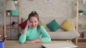 Positiv och lycklig tonårs- flicka i en defekt- eller brännskadaframsida som talar på telefonen lager videofilmer