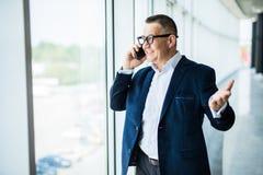 Positiv säker lyckad hög affärsman i formellt dräktanseende på fönstret och beskådacityscape, medan tala på mo royaltyfri fotografi