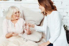 Positiv sjuksköterska som hemma besöker den sjuka kvinnan royaltyfria bilder