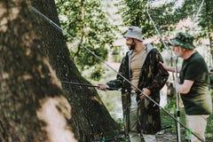 Positiv skäggig man som fiskar med hans åldriga fader fotografering för bildbyråer