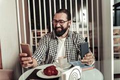Positiv skäggig pärla som samtidigt rymmer två smartphones fotografering för bildbyråer