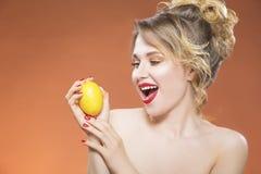 Positiv skämtsam Caucasian naken flicka som poserar med den gula citronen Arkivfoto