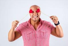 Positiv stilig man på en vit bakgrund med hjärtor i hans ögon, en vykort för dag för valentin` s, emotionellt foto Arkivbild