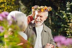 Positiv trevlig kvinna som sätter en krans på hennes makehuvud royaltyfri bild