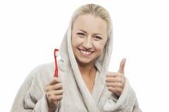 Positiv ung blond kvinna med manuella tandborstevisningtummar royaltyfria bilder