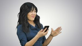 Positiv ung härlig asiatisk kvinna som använder mobiltelefonen, dans och att le på vit bakgrund lager videofilmer
