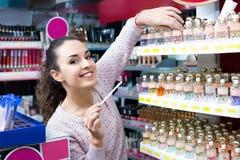 Positiv ung härlig kvinna som väljer doft Arkivfoto