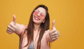 Positiv ung kvinna som gör en gest tummen-upp fotografering för bildbyråer