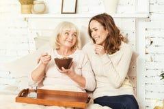 Positiv ung kvinna som kopplar av med att åldras farmodern hemma Arkivfoton