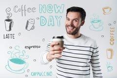 Positiv ung man som rymmer ett exponeringsglas av kaffe och ser lycklig fotografering för bildbyråer