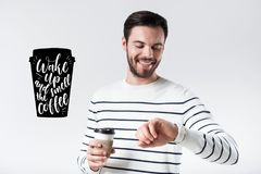 Positiv ung man som ser hans klocka, medan dricka kaffe royaltyfria bilder
