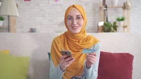 Positiv ung muslimsk kvinna för stående i hijab som ler rymma smartphonen, och kontokort som sitter på soffan i vardagsrum på arkivfilmer