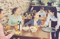 Positiv ung servitrisportionfamilj i familjkafé arkivfoton