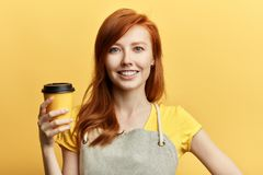 Positiv ursnygg flicka som erbjuder en kopp kaffe arkivbild