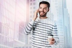 Positiv vänlig man som talar på telefonen, medan dricka kaffe Royaltyfri Foto