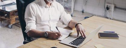 Positiv vuxen affärsman som använder den mobila bärbar datordatoren, medan sitta på trätabellen på det moderna coworking stället  royaltyfri fotografi