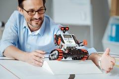 Positiv vuxen tekniker som testar roboten i en labb Royaltyfria Bilder