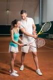 Positiv yrkesmässig instruktör som lär att spela tennis Fotografering för Bildbyråer