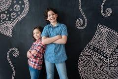 Positiva barn som står med deras korsade armar och att le arkivfoto