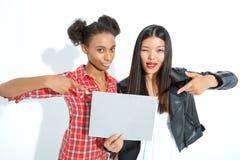 Positiva flickor som rymmer arket av papper royaltyfri fotografi