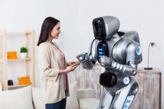Positiva flickor som står med roboten Arkivbilder