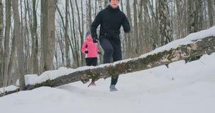Positiva härliga unga sunda par som kör med sportswearen till och med skogen i den soliga vintermorgonen hopp stock video