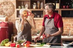 Positiva höga par som har gyckel på kök royaltyfria foton