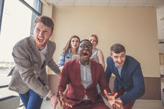 Positiva kollegor som har gyckel med kontorsstolar Arkivfoto