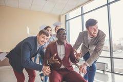 Positiva kollegor som har gyckel med kontorsstolar Royaltyfri Bild