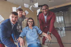 Positiva kollegor som har gyckel med kontorsstolar Royaltyfri Fotografi