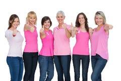 Positiva kvinnor som bär rosa färger för att posera för bröstcancer Fotografering för Bildbyråer