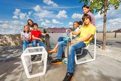 Positiva ungar sitter på vita stolar med skateboarder Fotografering för Bildbyråer