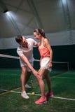 Positiva vänner som lär att spela tennis Royaltyfri Foto