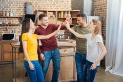 Positiva vänner som skrattar, medan ge fem till varandra Arkivbild