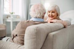 Positive ältere Frau, die ihr Ehemanngesicht betrachtet lizenzfreie stockfotos
