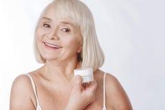 Positive ältere Frau, die mit Falten kämpft lizenzfreie stockbilder