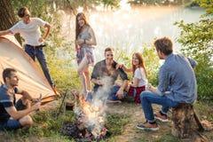 Positive abenteuerliche Leute warten auf die Vorbereitung des Abendessens stockfoto