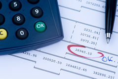 Positive account. Calculator with 'ok' button and a pen on an account sheet Stock Image