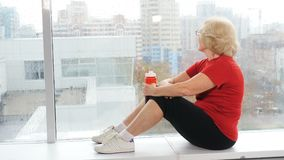 Positive and active aged woman sitting on window sill of gym resting after training. Panoramic windows in background
