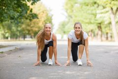 Beautiful, sports girls exercising on a park background. Fitness lifestyle concept. Copy space. royalty free stock images