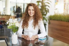 Positive adorable woman with appealing look, dressed in white blouse, recretats in cozy cafe decorated with flowers and green plan. Tation, drinks takeaway Stock Image