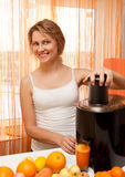 Positive adult girl making juice Royalty Free Stock Image