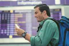 Positive adult guy is waiting for flight Royalty Free Stock Photo