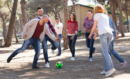 Positive adults chasing ball outdoors Royalty Free Stock Photos