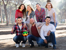 Positive adults chasing ball outdoors Royalty Free Stock Photography