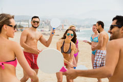 Positive adults with rackets relaxing at beach Royalty Free Stock Photo