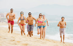 Positive adults running at sandy beach Royalty Free Stock Photos