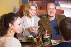 Positive adults with wine and dinner laughing in restaurant Royalty Free Stock Photography