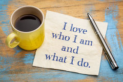 Positive affirmation words on napkin with coffee. I love who I am and what I do - positive affirmation text on a napkin with a cup of coffee stock photos
