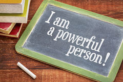 Positive affirmation words on slate blackboard. I am a powerful person - positive affirmation words on a slate blackboard with chalk and books against rustic stock image
